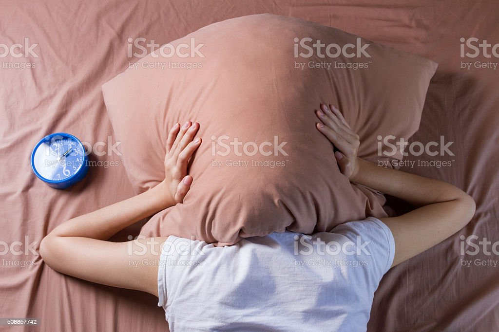 woman cover her head with pillow stock photo
