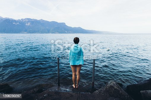 istock Woman covered by towel resting after swimming in the mountain lake staying at the lakeshore in Switzerland 1206230257