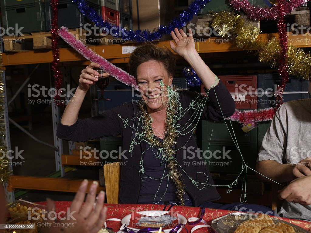 Woman covered in party streamers laughing at charismas table in warehouse royalty-free stock photo