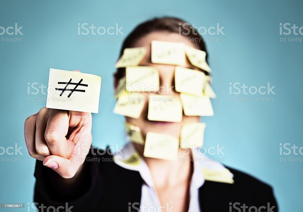 Woman covered in sticky-label reminders holds up # symbol royalty-free stock photo
