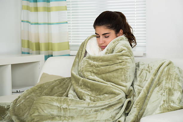 Woman Covered With Blanket Suffering From Cold stock photo