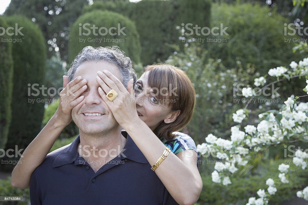 Woman covering boyfriends eyes royalty-free stock photo