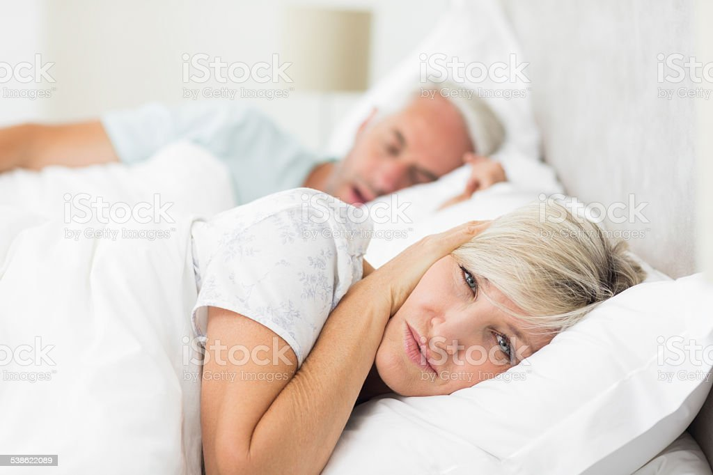 Woman covering ears while man snoring in bed stock photo