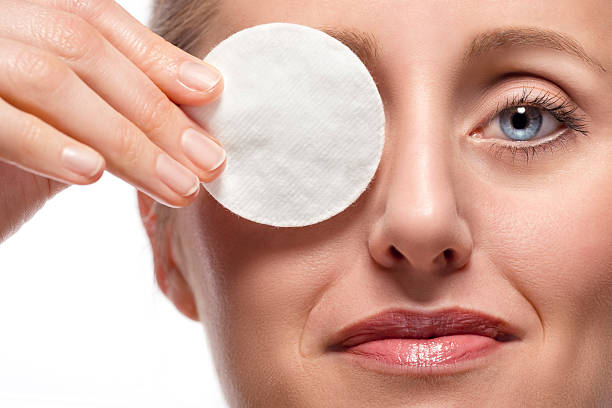 Woman covering eye with cotton pad stock photo