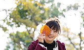 Woman covering eye with hibiscus leaf in autumn.