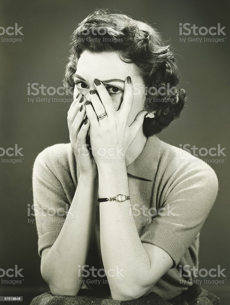 Woman covering face, peeping through fingers, (B&W) stock photo