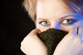 Close-up portrait of beautiful woman covering his face with the sweater. Blue light reflections.