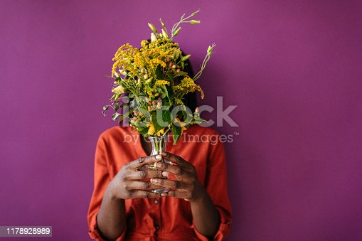 Unrecognizable African Woman covering face with bouquet in vase on purple background