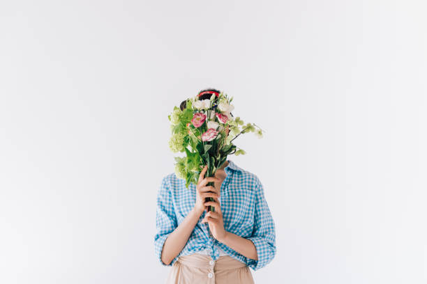 woman covering face with flowers stock photo