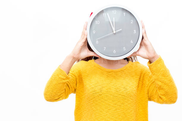 Woman covering face with watch Woman covering face with watch showing time before New Year. Girl in yellow sweater holding watch while waiting to finish sales. Time is running out concept information sign stock pictures, royalty-free photos & images