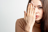 istock Woman covering half face with hand 1256487461