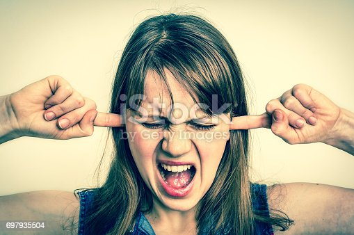istock Woman covering her ears to protect from loud noise 697935504