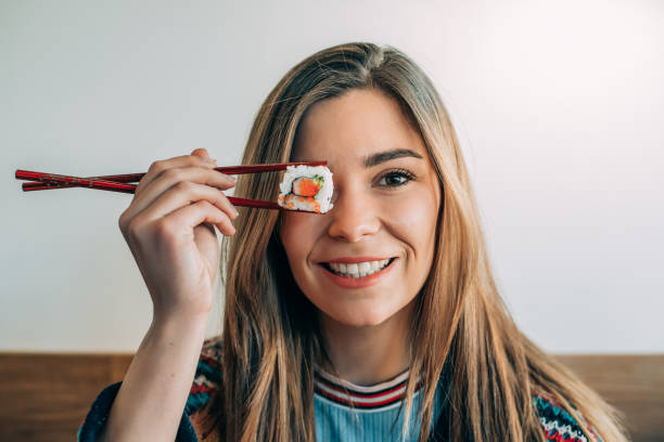 woman covering her eye with piece of sushi stock photo
