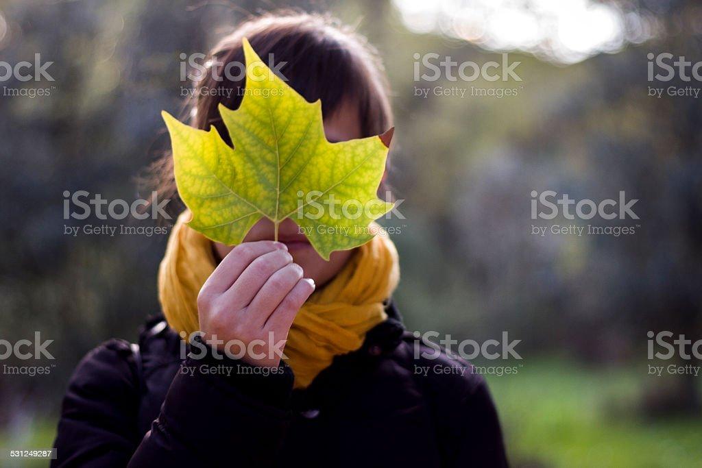 Mujer que cubre la cara con una hoja - foto de stock