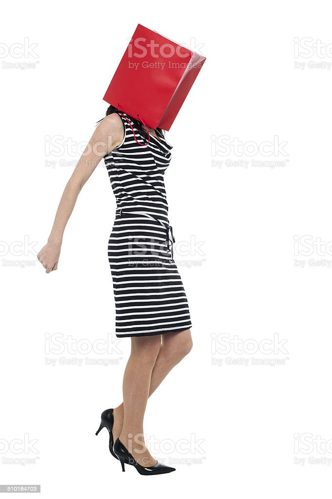 Woman covering her face with shopping bag stock photo