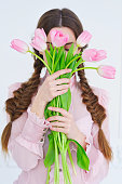 Young woman with trendy two braids hairstyle holding a bunch of pink tulips in front of her face