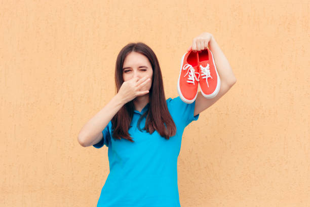 Frau bedeckt Nase hält ein Paar Stinky-Schuhe – Foto