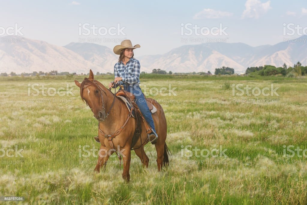 Woman Cowgirl riding on horse along ranch grassland stock photo