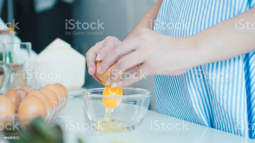 Woman cracking an egg into a bowl with  standing by in kitchen. Mother pregnant cooking in kitchen. - Royalty-free Adult Stock Photo