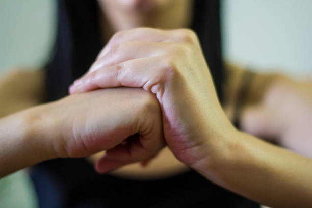 woman cracking their knuckles - knuckle stock photos and pictures