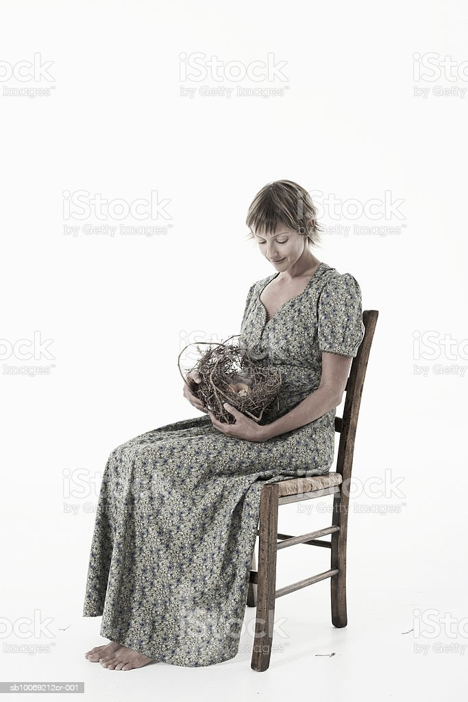Woman cradling nest with eggs against white background royalty free stockfoto