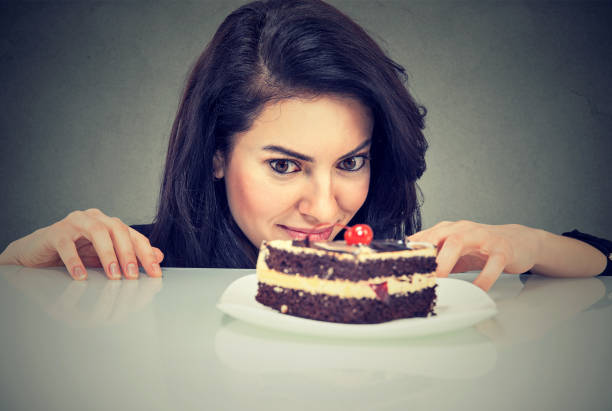 Woman craving cake dessert, eager to eat, isolated on gray background Woman craving cake dessert, eager to eat, isolated on gray background greed stock pictures, royalty-free photos & images