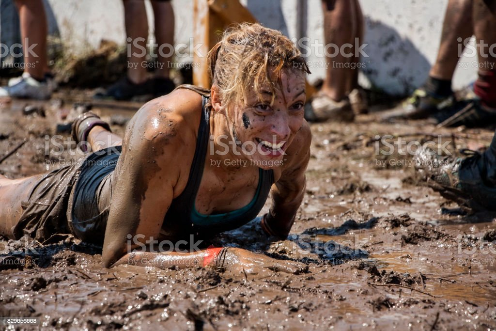 Woman crawling among mud in extreme sport competition stock photo