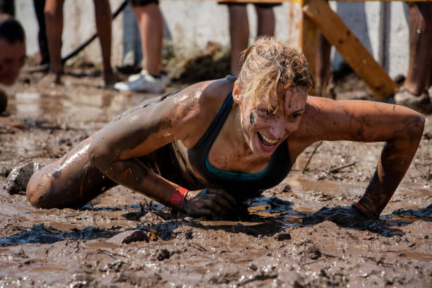 A woman crawling under barbed wire Young woman smiling and crawling under barbed wire; concept of winning, endurance, strength and fun obstacle course stock pictures, royalty-free photos & images