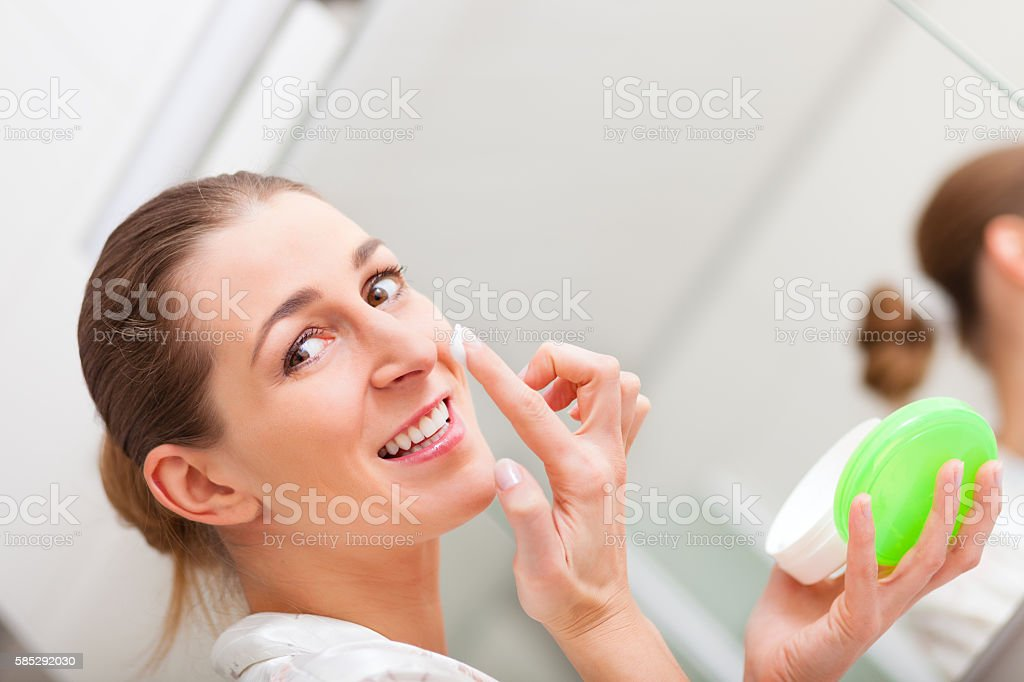 Woman creaming her face stock photo