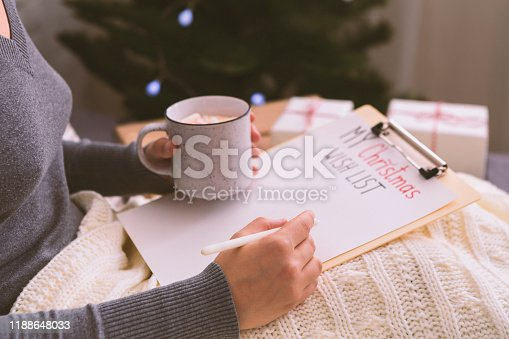 Woman creating her Christmas wish list for Santa, home interior, blurred background, copy space