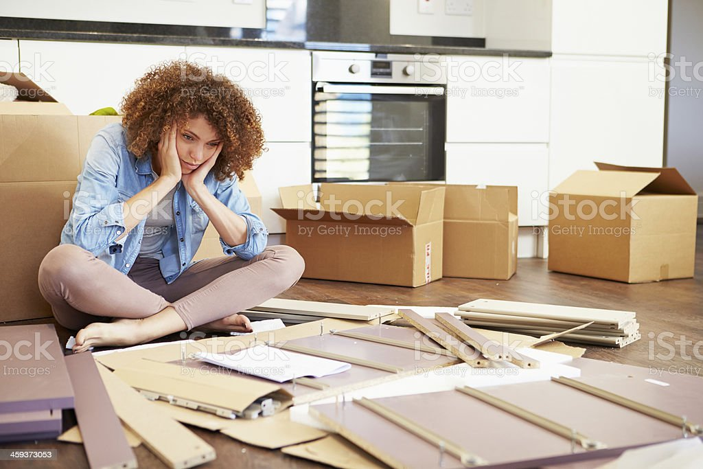 Woman cross legged in front of self assembly furniture stock photo