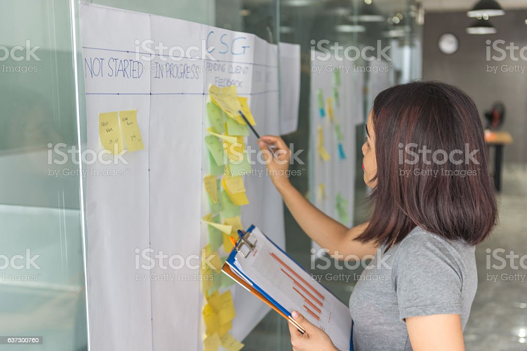 Woman cross-checking information in document with sticky notes stock photo
