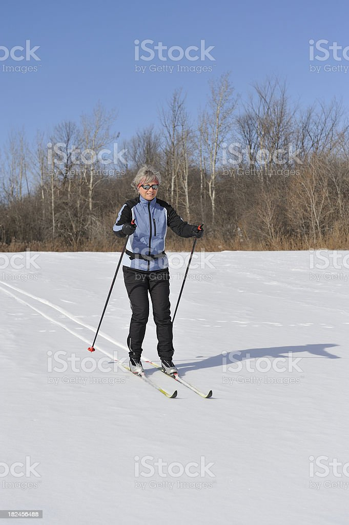 Mature woman skiing on a beautiful day. Fluorescent strips on the...