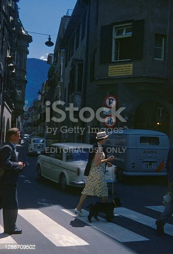 Bolzano, South Tyrol, Italy, 1962. Woman crosses a zebra crossing with her dog. So: other passers-by, cars and buildings.