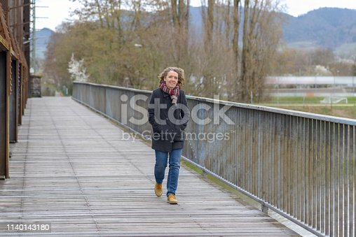 Woman crossing a bridge walking towards the camera with her hands in the pockets of her warm winter coat on a cold grey day