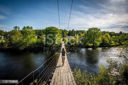 Woman walking on a wire footbridge