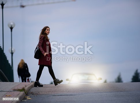 Woman crossing road dark bridge, car in background