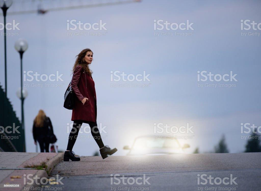 Frau Kreuzung dunkle Straßenbrücke, Auto im Hintergrund – Foto