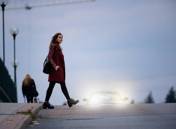 vrouw kruising donkere verkeersbrug, auto op achtergrond - oversteken stockfoto's en -beelden