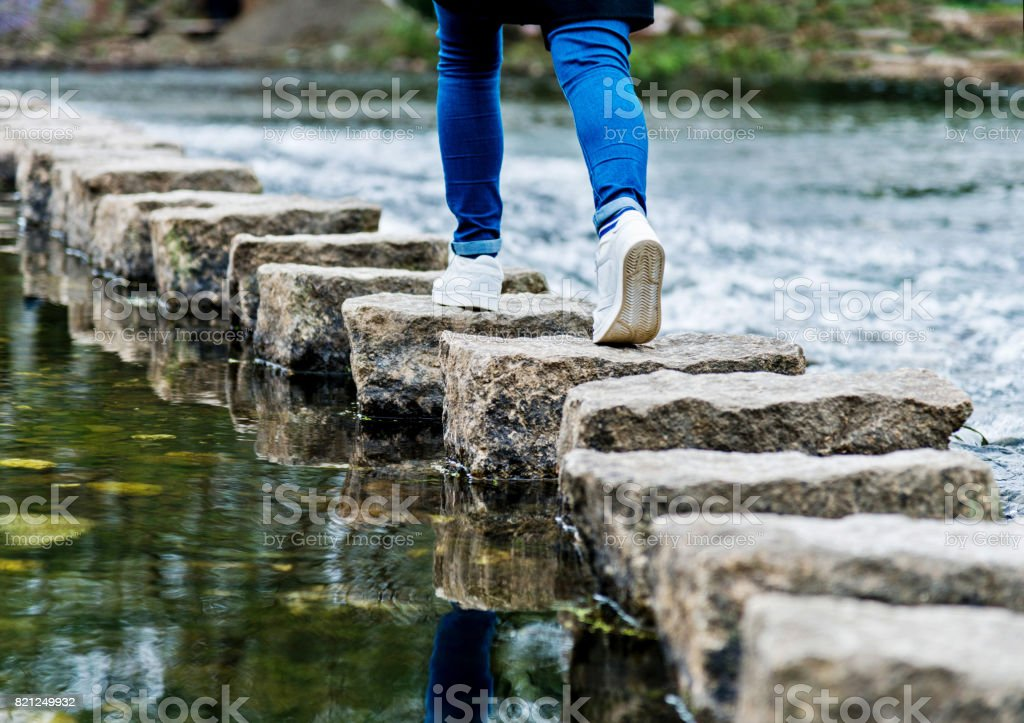 Woman crossing stepping stones on a river stock photo