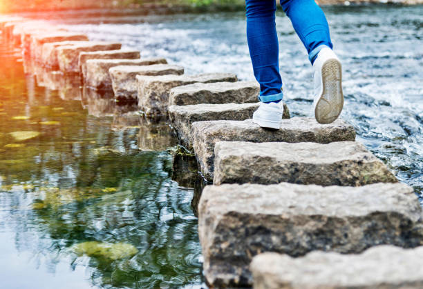 Woman crossing stepping stones on a river Woman crossing stepping stones on a river stepping stock pictures, royalty-free photos & images
