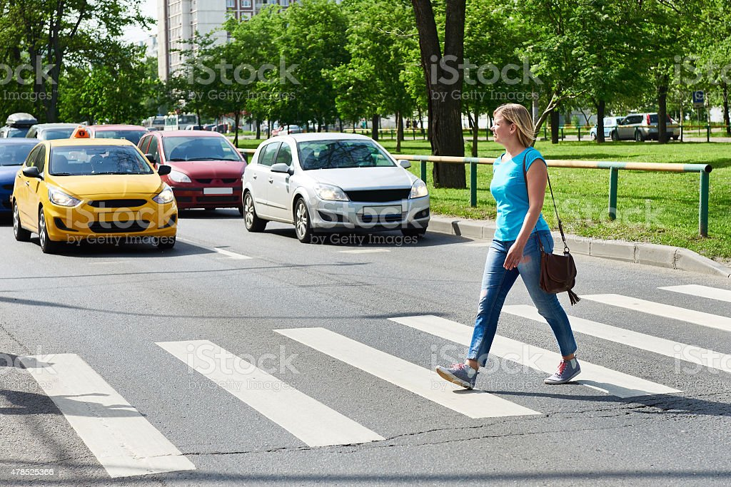 Woman crossing the street at a pedestrian crossing
