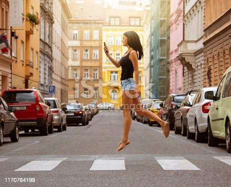Woman crossing street, jumping, checking phone