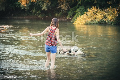 A caucasian girl in summer shorts crossing the river