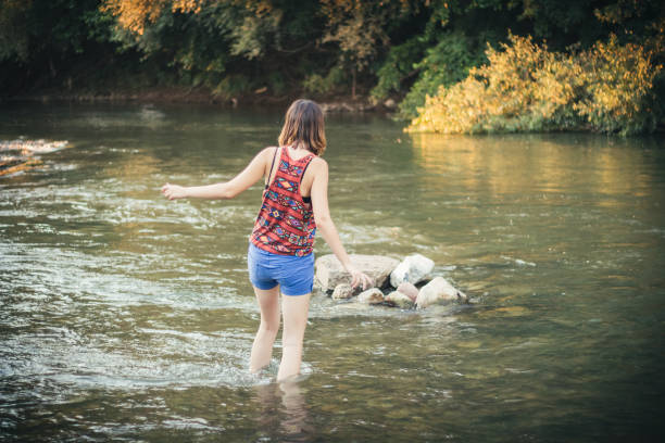Woman crossing the river A caucasian girl in summer shorts crossing the river wading stock pictures, royalty-free photos & images