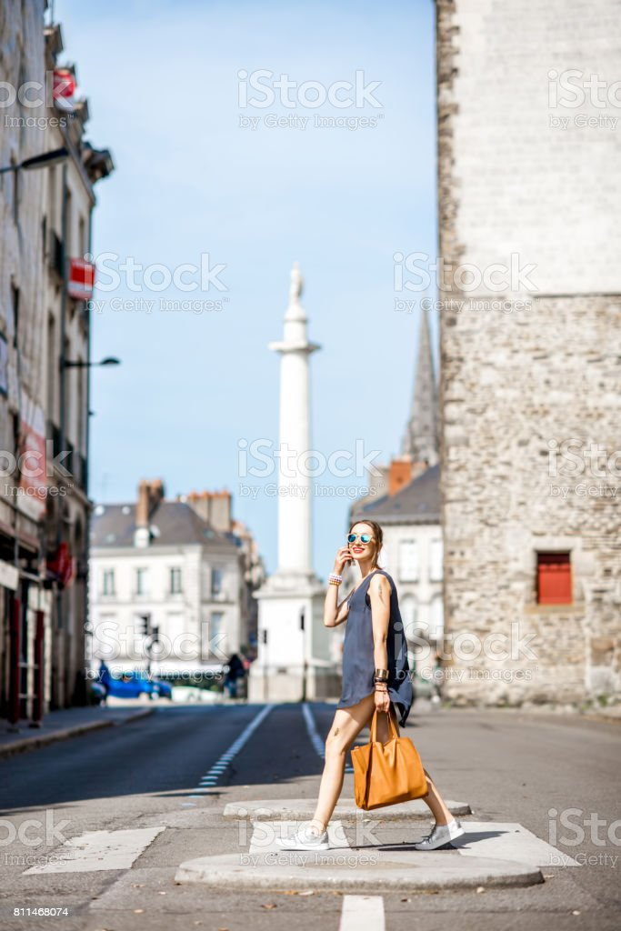 Woman crossing the street in the old city stock photo