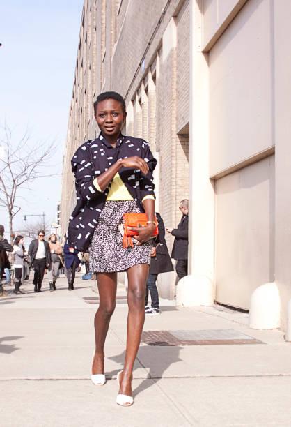 vrouw oversteken van de straat te praten over haar mobiele telefoon in new york city - street style stockfoto's en -beelden