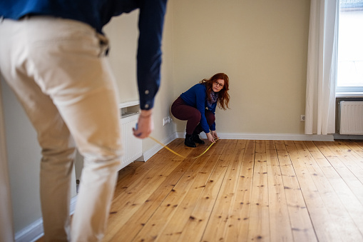 Redhead woman crouching while measuring hardwood floor with man. Couple is analyzing new home together. They are at empty apartment.