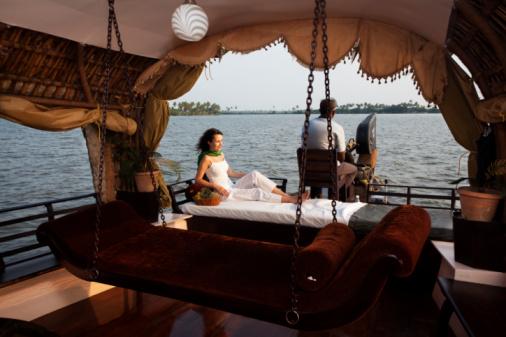 woman lying enjoying houseboat tour e backwaters in Kerala state india