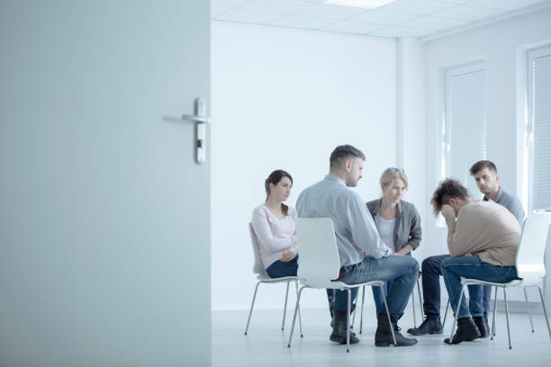 Woman crying in rehab center Woman crying while sitting in circle during meeting with support group in rehab center drug rehab stock pictures, royalty-free photos & images